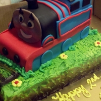 Thomas Train 2 quarter sheet cakes cut and covered with fondant on top of a quarter sheet cake piped with buttercream grass and airbrushed
