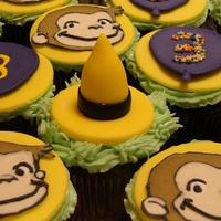 Curious George Cupcakes chocolate cupcakes topped with fondant yellow circles and fondant yellow hats. Balloons and George faces made out of royal icing. Some of...