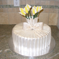 Pleated Flower Cake  Pleated fondant wraps around the cake. Topped with a gumpaste collar and stenciled bow, the cake showcases hand molded calalilies. The gift...