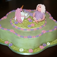 Unicorn Birthday Cake Pedal shaped buttercream cake with fondant topper. Little girl and unicorn on a stone textured round.