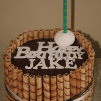 Golf Theme Birthday Flourless chocolate cake with raspberry filling, swiss butter cream, covered with ganache and cookies around the side. I tied a simple...