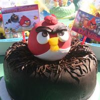 Angry Bird Birthday Cake Red Angry Bird sitting on a chocolate twig nest on top of a wood-grained textured trunk.