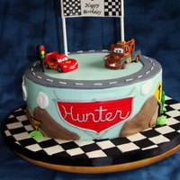 "Hunter's 1St Bd Cars Cake Cake is a 10"" french vanilla with pineapple chiffon filling, covered in WC ganache and then fondant. Cars on top were purchased,..."