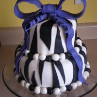 Zebra Cake white and chocolate cake w/ cream cheese buttercream, coverred in mmf. Fondant bow and fondant for zebra stripes.