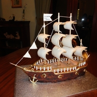 Sailing Ship the ship made by chocolate cake & covered by chocolate , fondant . sails , anchor all made by gumpase except the wooden sticks and the...