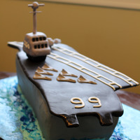 Uss America 6 9x13 cakes torted, filled and stacked. The top deck is cardboard covered in black fondant. The bridge was RKT covered in gum paste. The...