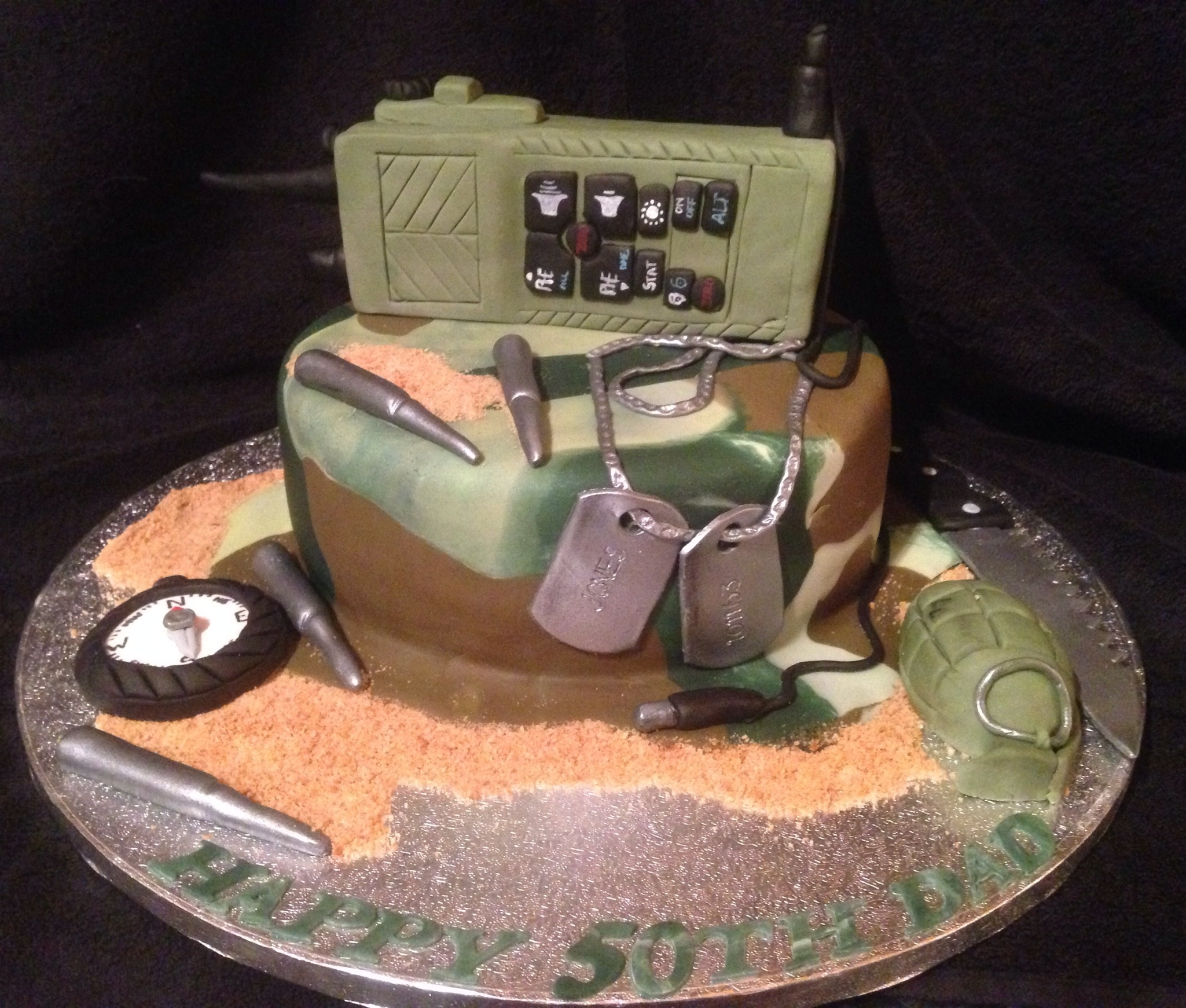 Army Style Cake With Walkie Talkie Grenade Compass Bullets Dog Tags And Knife Army style cake with walkie Talkie, grenade, compass, bullets, dog tags and knife.