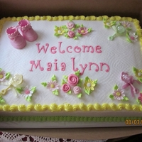 Baby Girl Shower Cake Baby shower cake, half stawberry, half vanilla buttercream icing, fondant flowers, and cupcakes to match