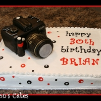 Camera Sheet cake with a nikon camera on top. All cake. The body of the camera is two sections cut from a 9x13 and stacked. The lens is a loaf pan...