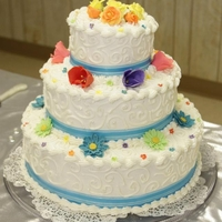 Colorful Floral Buttercream with multi colored fondant flowers and blue ribbon.
