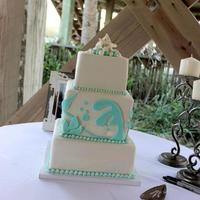 "Beachside Wedding All white cake with aqua ""undersea"" shapes. Topper is two white chocolate starfish with some ""water"" and some smaller..."