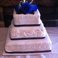Blue And Silver  3 Tier square wedding cake with navy blue and silver accents. Scroll work and dots are made of royal icing, and accented with silver...