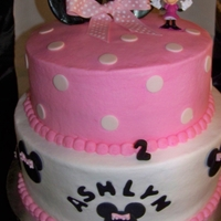 "Minnie Mouse This is an 10"" & 8"" chocolate and yellow cake. Iced in bc with fondant minnie face, ears and letters."