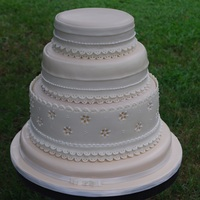 Eyelet Lace Wedding Cake This cake was covered in an ivory colored fondant. We then added white fondant bands. Royal icing was also used for some smaller details....