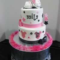 Mila Made to match the invites. All fondant with fondant decorations and baby converse shoes as the topper. Thanks =)