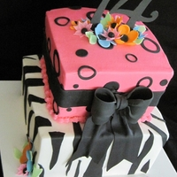 Zebra/pink/bows   8 inch, and 6 inch, buttercream with fondant accents. Numbers, bow, and flowers are 50/50.
