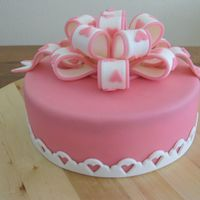 Pink With A Bow Pink cake filled with strawberry mousse and covered in marzipan and fondant bow.