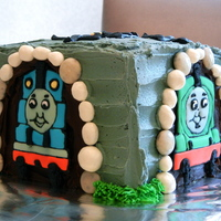 Thomas And Other Tank Engine Cake trains made from royal icing, iced in grey buttercream with yogurt raisins and other candy as the outline of the tunnel.