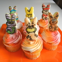 Dr Seuss Peep Toppers On Vanilla Cupcakes dipped peep pops in candy melt with characters done in edible writers