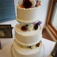 Daughter's Wedding Cake My first cake for an event was this wedding cake for my daughter. 3 tiered, multi-flavor, Zambito frosting, simple piping and real flowers...