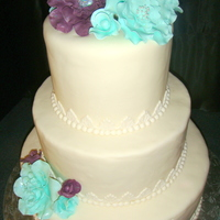 Wedding Cake For Riverboat Venue Three tiered, round wedding cake with gumpaste flowers in mint & plum colors. Made for a wedding on a riverboat.