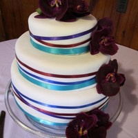 Ribbon Wedding Cake This cake is fondant covered then has satin ribbons in the wedding colors and silk flowers.