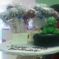 Spiderman, Dinosaur, Truck Cake  My customer needed a cake for a boy who couldnt make up his mind so we made him spiderman cake pops, a monster truck tire, and a dinosaur....