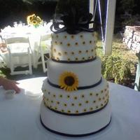 Sunflower Theme Wedding Cake round fondant covered wedding cake. quilted pattern with fondant mini sunflowers and large sunflower. fondant bow