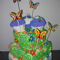 Butterfly Garden Four layer Chocolate cake with buttercream icing. Butterflies are hand painted fondant. vines and leaves are buttercream. Flowers are...