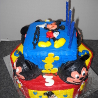 Third Birthday Mickey Mouse Cake Hexagon base four layers of chocolate with bc icing.. Second layer made of four layers chocolate and four dome shaped cakes.. Figures hand...