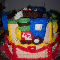 Trains Cake Hexahedron two layer orange cream cake with a second tier square two layer cake. Each train is a separate orange cake. Iced in bc.