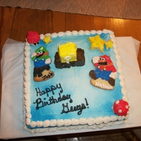 Mario Vs Luigi cake is butter cream with rice krispie mushrooms and blocks and stars. Mario and Luigi are made from sugar cookies.