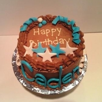 Boy's Birthday Cake Fondant stars and name adorn small chocolate cake.