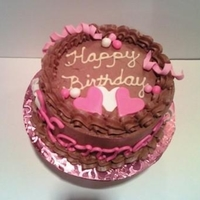 Girl's Birthday Cake Pink fondant hearts and name adorn small chocolate cake.