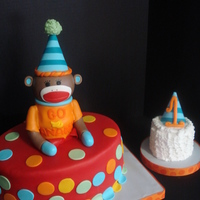 Jacob's Sock Monkey 1St Birthday Cake This cake matches the party plates used for his birthday party. The oval cake is covered in fondant and the sock monkey's body and...