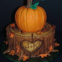 Fall Themed Anniversary Cake Stump and pumpkin both carved from cake and decorated with buttercream, then airbrushed. Fondant leaves and modeling chocolate pumpkin stem...