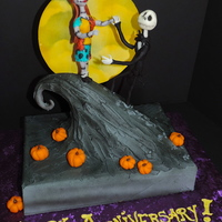Nightmare Before Christmas' Jack And Sally Cake  A great anniversary cake for Nightmare fans! Figures made with modeling chocolate on wire skeletons. Hill is a RKT chunk covering in hard...