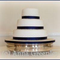 Round Diamante And Blue With Iced Accents Simple cake with diamante ribbon and iced accent dots.