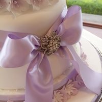 Lilac Flowers And Ribbon Wedding Cake Lilac themed wedding cake with flowers, ribbon and beadwork