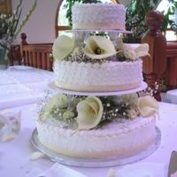 Plain White Wedding Cake Plain white cake, buttercream filling and icing with pearl & ribbon accents.