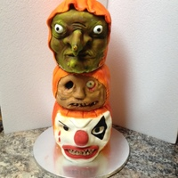 Scary Faced Pumpkin Cakes three stacked ghoulish faced pumpkin cakes, a demonic clown, a ghoul and a witch