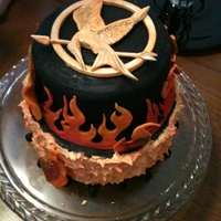 Hunger Games Inspired Birthday Cake The Pin Is Gum Paste Flames Are Fondant And Buttercream Hunger Games inspired birthday cake. The pin is gum paste. Flames are fondant and buttercream.