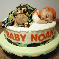 "3-D Baby Camo Cake  12"" marble cake, iced in butter cream with fondant and gum paste decorations. Baby is carved cake with fondant shoulders, blanket..."