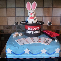 Magic Show Birthday Cake 2 layer, 11x15 inch cake base, topped with a rice krispy treat top hat and rabbit covered in fondant; with gumpaste playing cards, dice and...