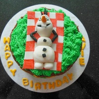 Olaf Birthday Cake Chocolate cake with fondant Olaf on a fondant blanket and buttercream grass.