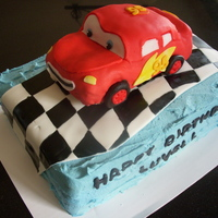 "Lightning Mcqueen Cake Lightning McQueen made from rice krispy treats and covered in fondant, atop a 2 layer, 9x13"" cake iced in pale blue buttercream and..."