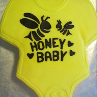 Honey Baby Onesie Gender neutral yellow onesie cake for a bumble bee themed baby shower. Cake is coloured yellow and lemonade flavoured