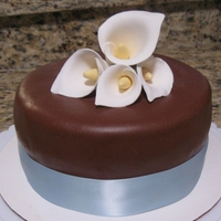 Simple Calla Lilly Cake Feb 2011: Choc Fudge cake with coffee icing. Brown MMF, blue ribbon, and gumpaste Calla Lillies. Quick and simple!