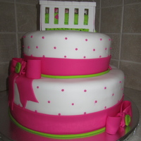 "Pink/lime Baby Shower Cake   12"" and 9"" cakes with fondant bows, frosting dots, and gumpaste crib/baby on top"