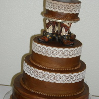 Nikki   White bridal cake with buttercream icing. Fondant belt. Lace accents. Middle tiers are dummy cakes.